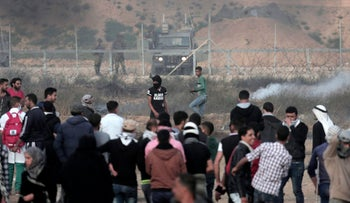 Palestinian protesters gather while Israeli troops fire teargas near the fence during a protest at the Gaza Strip's border with Israel, April 27, 2018.
