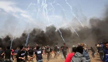 Palestinian demonstrators run for cover from tear gas fired by Israeli security forces during the fifth consecutive mass Gaza border demonstration, April 27, 2018.