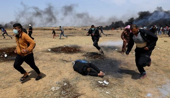 A wounded Palestinian falls on the ground during clashes with Israeli troops at a protest at the Israel-Gaza border in the southern Gaza Strip, April 27, 2018