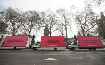 Vans with slogans aimed at Britain's Labour Party are driven around Parliament Square ahead of a debate on antisemitism in Parliament, in London, April 17, 2018.