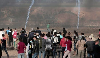 A Palestinian protester hurls stones at Israeli troops as others gather during a protest at the Gaza Strip's border with Israel, April 27, 2018.