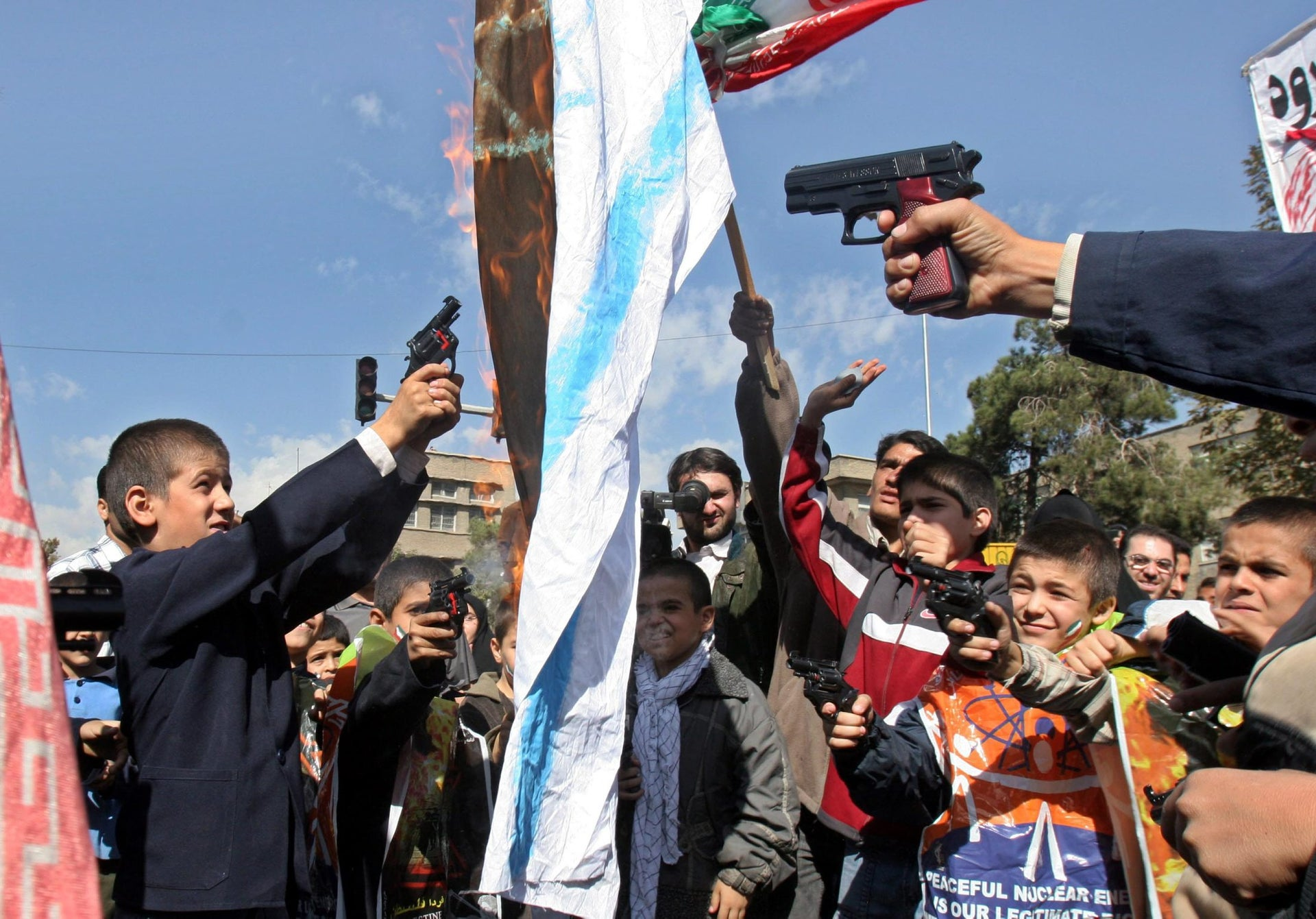 "Iranian schoolboys shooting toy guns at an Israeli flag as it burns during an anti-Israeli rally marking ""Al-Quds Day"" (Jerusalem Day), Tehran, Oct 2005."
