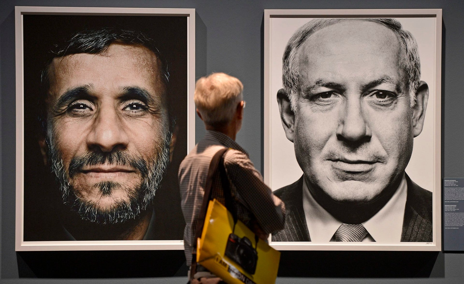 "A visitor looking at portraits of Iranian President Mahmoud Ahmadinejad and Israeli Prime Minister Benjamin Netanyahu during the exhibition ""Faces of Power"" in Cologne, 2012."