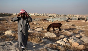 A Bedouin of the Jahalin tribe walks in his encampment near the Jewish settlement of Maale Adumim, June 16, 2012