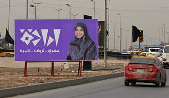 In this Thursday, Feb. 22, 2018, photo, a campaign poster of Iraqi lawmaker Hanan al-Fatlawi is seen in Baghdad, Iraq. Iraq's Shiites, Sunnis and Kurds have grown more fragmented and divided ahead of the national elections scheduled for May due to deep differences among each group that have spawned more and smaller alliances seeking to have a bigger share in the new parliament.
