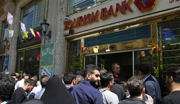 Iranians stand in front of a bank, hoping to buy U.S. dollars at the new official exchange rate announced by the government, in downtown Tehran, Iran, Tuesday, April 10, 2018.