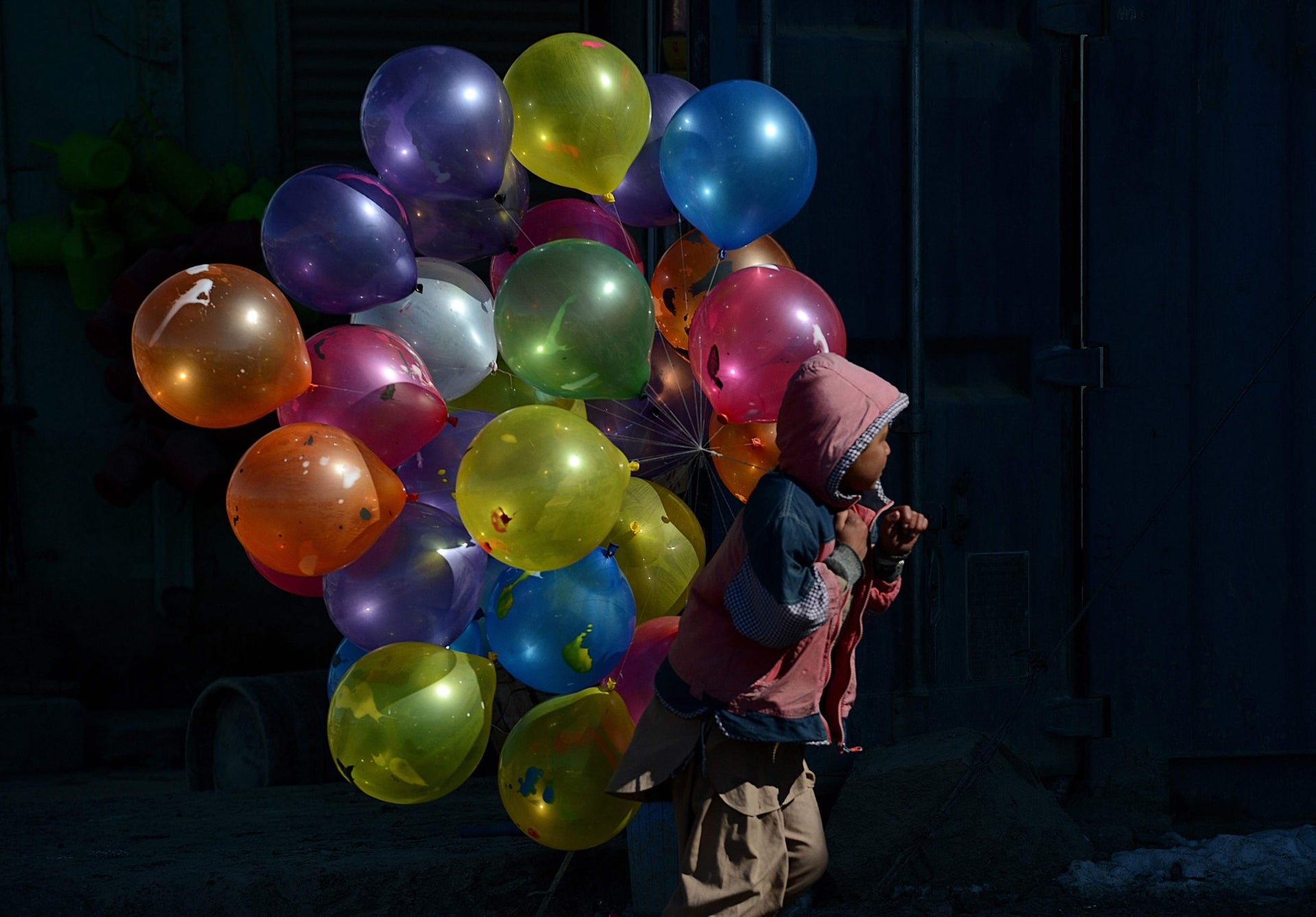 An Afghan boy walks with balloons for sale on a cold winter's day in Kabul, February 7, 2013.