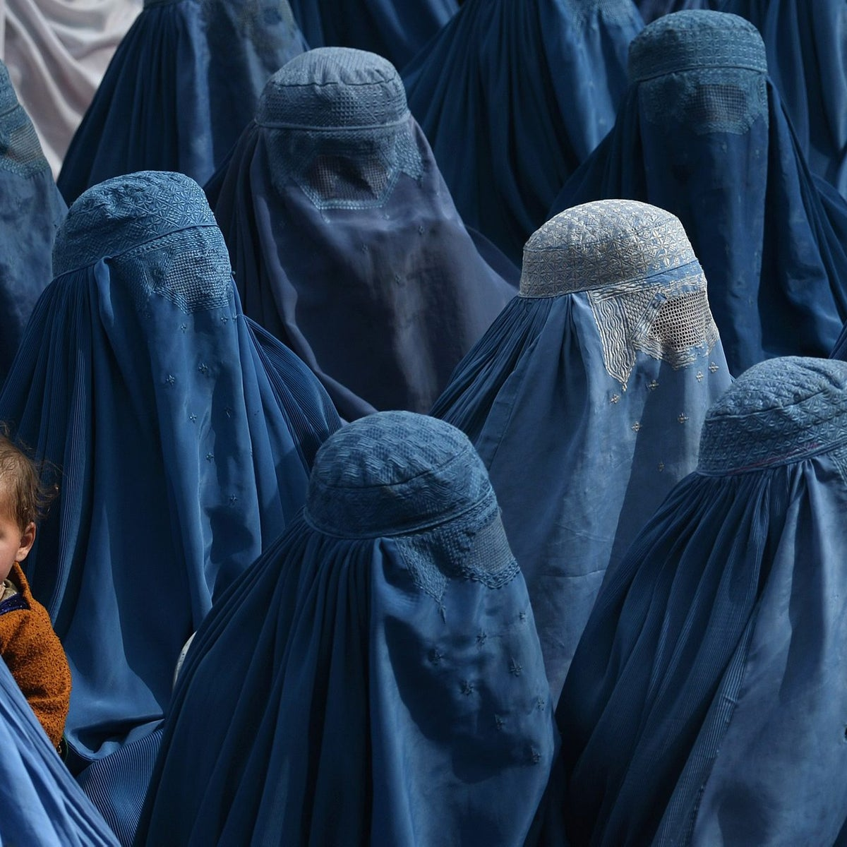 An Afghan woman holds her baby as she and supporters attend the election rally of Afghan presidential candidate Abdullah Abdullah in Jalalabad, February 18, 2014.
