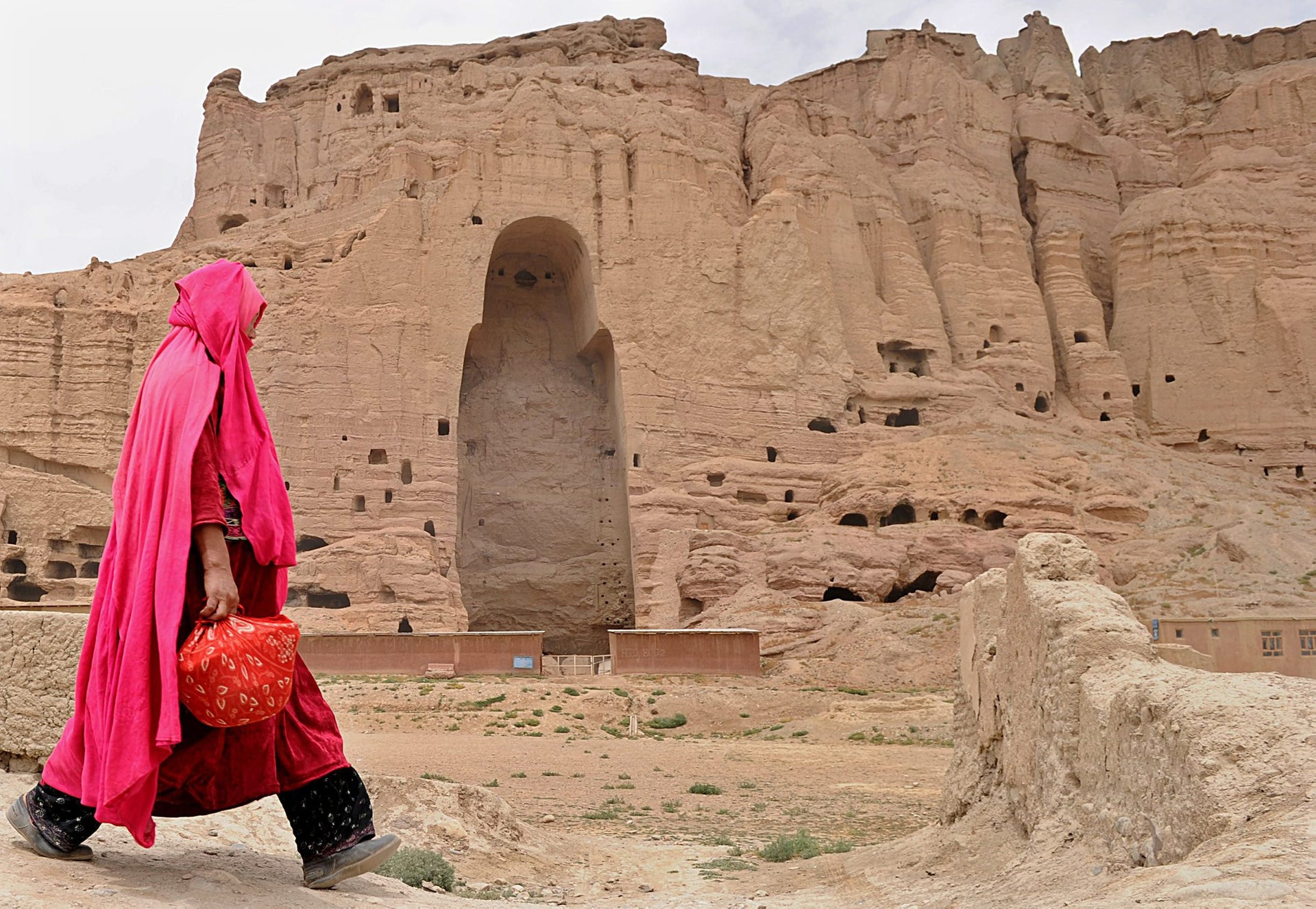 A Hazara Afghan woman walks past the ruins of the ancient Buddha statues that once stood in the city of Bamiyan, August 1, 2010.