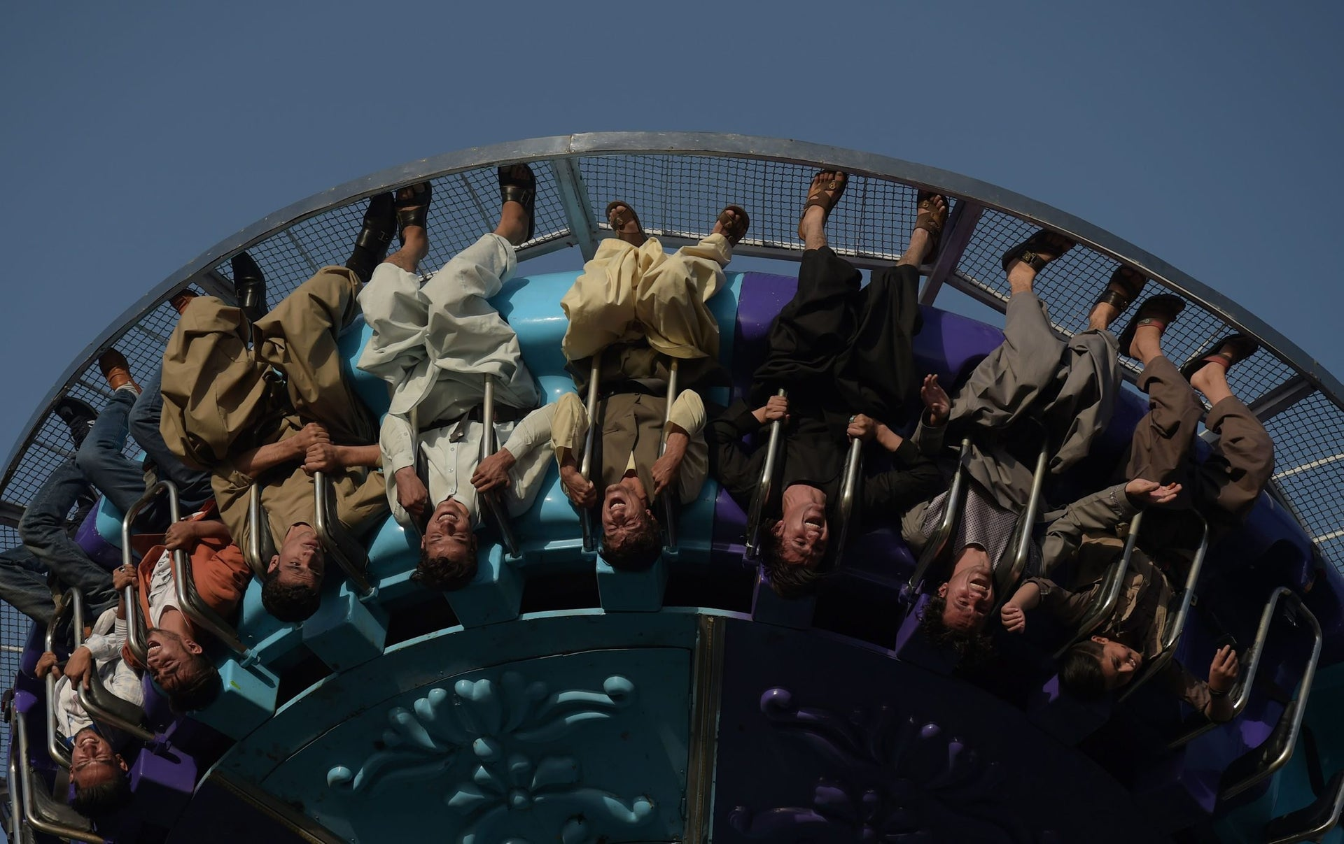 Afghan visitors ride a fairground ride at the Park Shahar or City Park in Kabul, September 6, 2017.