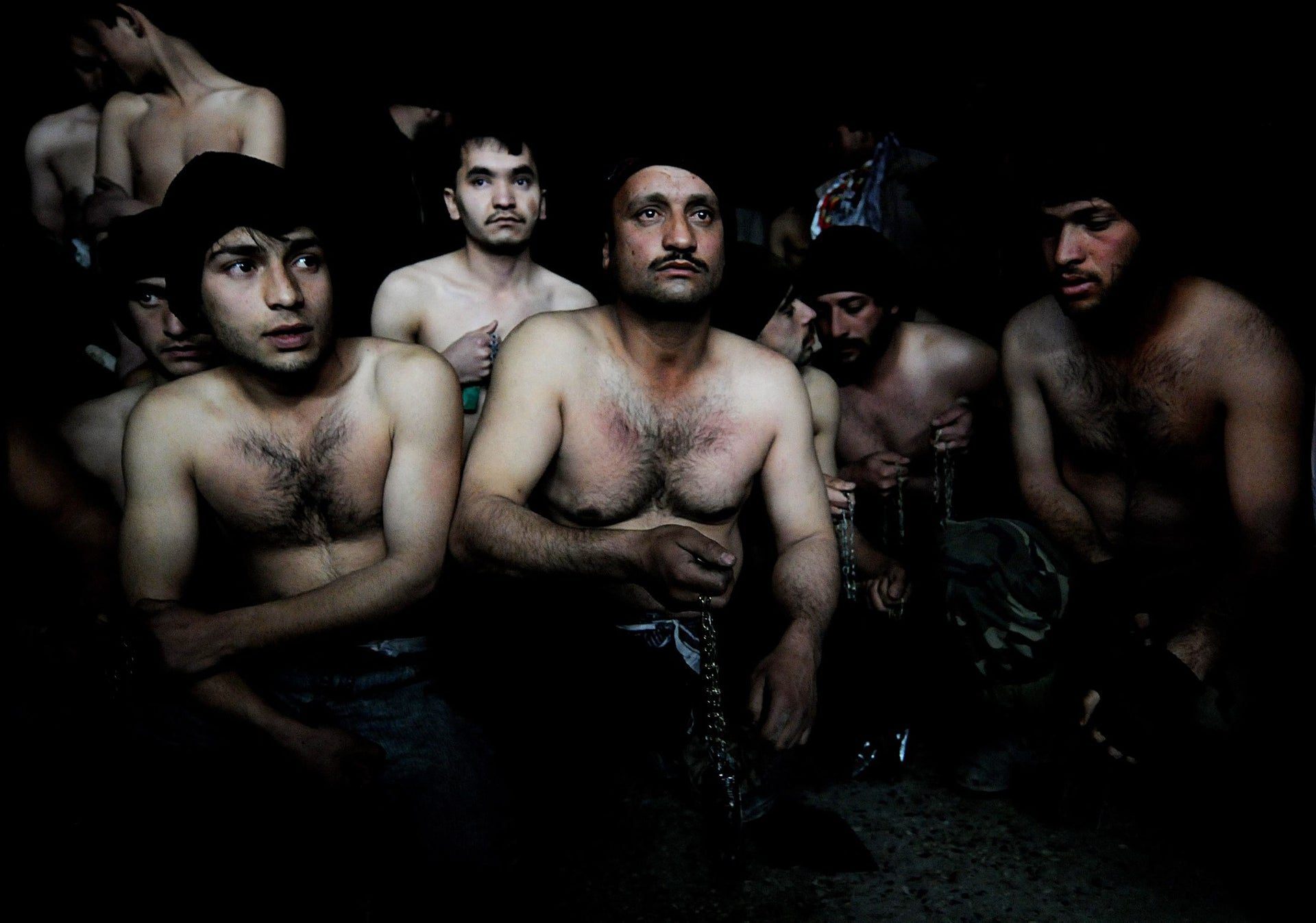 Afghan men hold chains as they wait to take part in ritual self-flagellation to celebrate the Muslim festival of Ashura, at a mosque in Kabul, January 15, 2008.