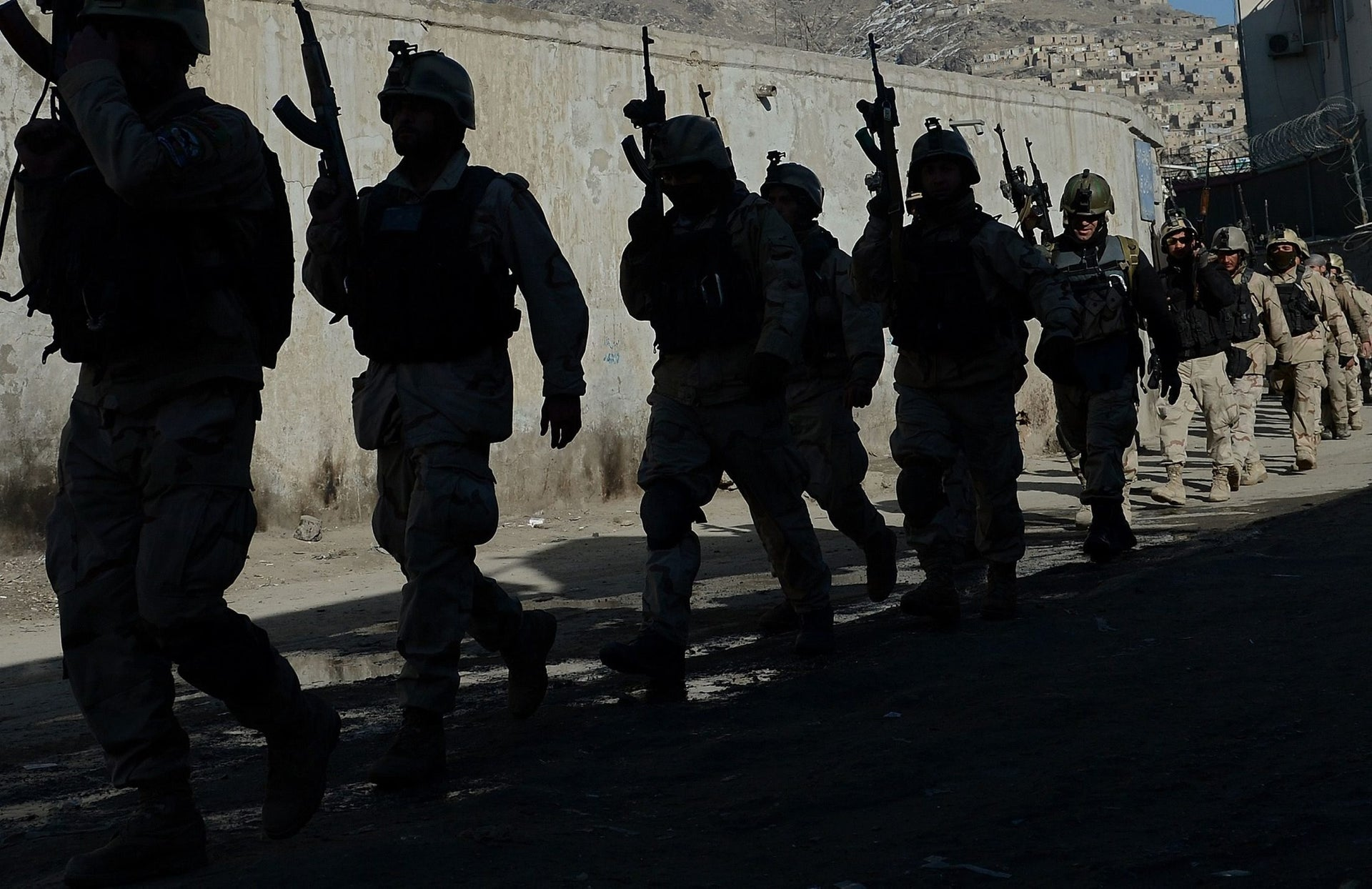 Afghan commandos walk down a road near the Kabul police headquarters building after a clash between Afghanistan forces and Taliban fighters in Kabul, January 21, 2013.