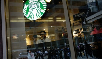 Protesters marching down Market Street are seen reflected in a Starbucks storefront in Philadelphia, a week after two black men were arrested at a Starbucks coffee shop