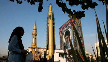 In this September 24, 2017 file photo, a Ghadr-H missile, a solid-fuel surface-to-surface Sejjil missile and a portrait of the Supreme Leader Ayatollah Ali Khamenei are displayed at Baharestan Square in Tehran.