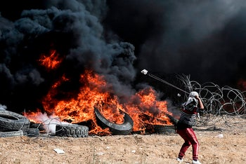 A Palestinian protester uses a slingshot during clashes with Israeli forces on the Israel-Gaza border, during the fifth straight Friday of mass demonstrations. April 27, 2018