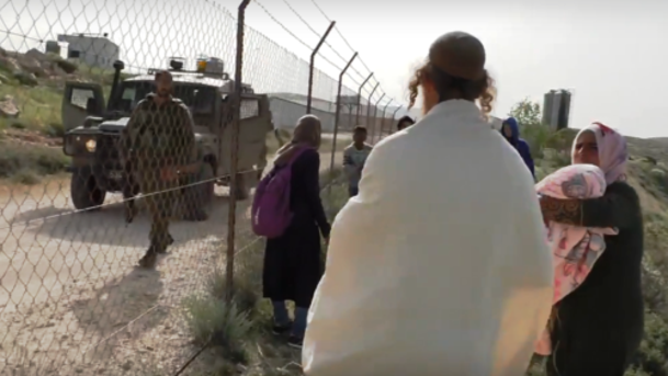Extremist settler harasses Palestinian children and mother in front of soldiersq