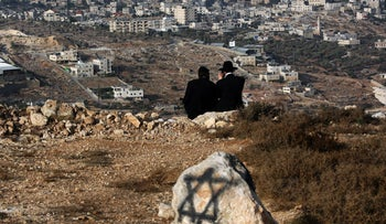 FILE PHOTO: Orthodox Jews sit looking at the view while right wing Israeli settlers attempt to establish an unauthorised outpost in Givat Eitam a hilltop above the Palestinian town of Bethlehem in the West Bank.