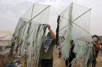 Palestinians prepare to set kites on fire to be thrown at the Israeli side at a protest at the Israel-Gaza border in the southern Gaza Strip, May 4, 2018.