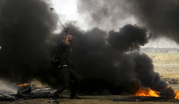 Palestinian protesters hurl stones at Israeli soldiers near the border fence east of Khan Younis on May 4, 2018.