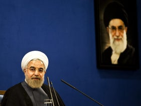 Iranian President Hassan Rouhani listens, sitting next to a portrait of supreme leader Ayatollah Ali Khamenei (R), during a press conference in Tehran on June 13, 2015
