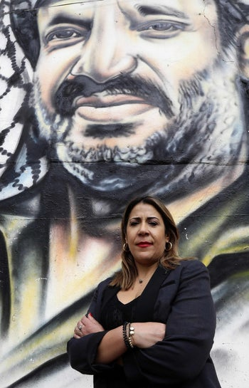 Palestinian parliamentary candidate Manal Kortam, who has nominated herself for a seat that does not exist in next month's elections to raise awareness about the situation of Palestinian refugees in Lebanon, poses for a picture in front of a graffiti of late Palestinian leader Yasser Arafat at the entrance of the Mar Elias Palestinian refugee camp in Beirut on April 26, 2018.