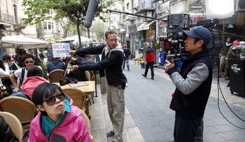 """A film crew from Chuan Films shoots footage of Chinese actors on the set of """"The Old Cinderella"""" at the Ben Yehuda pedestrian mall in Jerusalem, Israel, on Friday, April 19, 2013"""