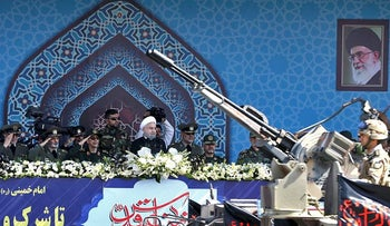 Iran's President Hassan Rouhani, center, reviews a military parade during the 37th anniversary of Iraq's 1980 invasion of Iran, in front of the shrine of the late revolutionary founder, Ayatollah Khomeini, just outside Tehran, Iran, Friday, Sept. 22, 2017