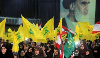 Female supporters of Lebanon's Hezbollah hold flags listening to their leader Sayyed Hassan Nasrallah as he speaks on a video screen in Beirut, Lebanon February 16, 2018