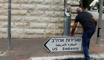 A worker holds a road sign pointing to the U.S. embassy in Jerusalem, in 2018. REUTERS/Ronen Zvulun