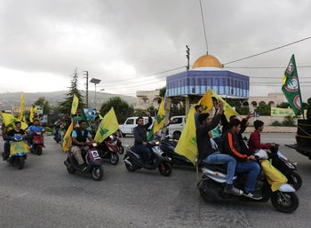 Supporters of Lebanon's Hezbollah and Amal Movement ride on motorbikes as they hold Hezbollah and Amal flags in Marjayoun, Lebanon, May 7, 2018.