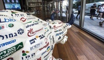 A bull sculpture decorated with Israeli company logos sits on display in the window of the Tel Aviv Stock Exchange in Tel Aviv, Israel, August 4, 2016.