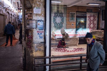 File photo: A man passes a carpet store worker in the rug bazaar of Tehran, Iran. Reinstated U.S. sanctions will limit the importation of rugs from Iran into the U.S.