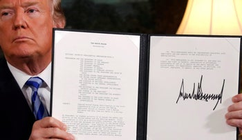 U.S. President Donald Trump holds up a signed proclamation declaring his intention to withdraw from the Iran nuclear deal in the Diplomatic Room at the White House in Washington, May 8, 2018.