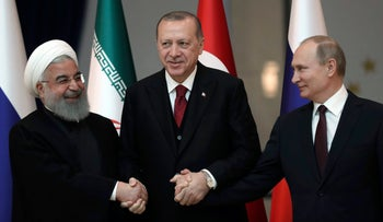 Iran's President Hassan Rouhani, Russia's President Vladimir Putin and Turkey's President Recep Tayyip Erdogan lock hands during a group photo in Ankara, Turkey. April 4, 2018.