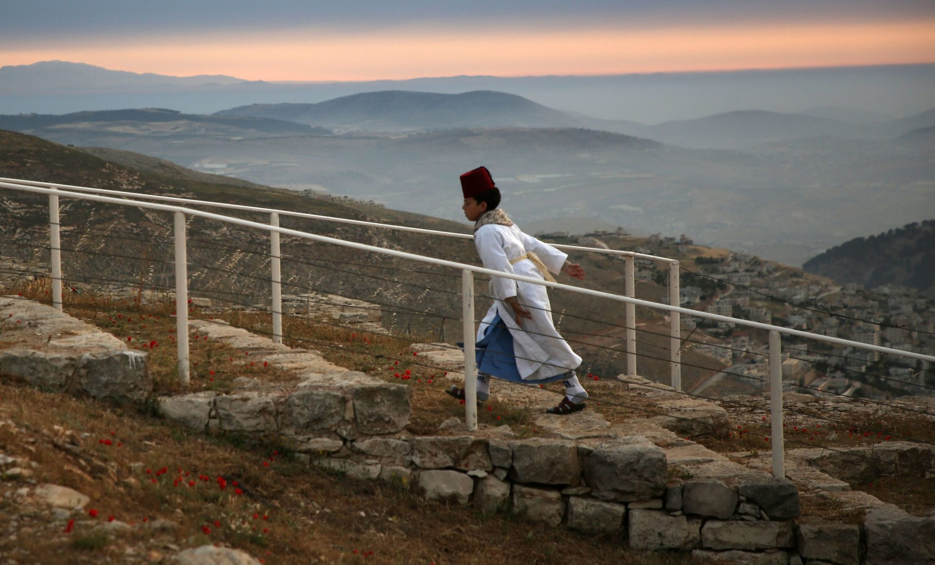A young Samaritan worshipper walking up Mount Gerizim to participate in an early morning Passover ceremony, May 6, 2018.