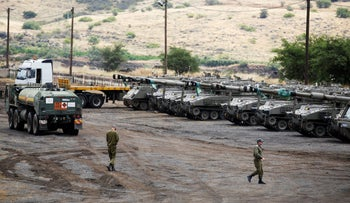 Israeli soldiers walk near mobile artillery units in the Golan Heights, Israel May 9, 2018