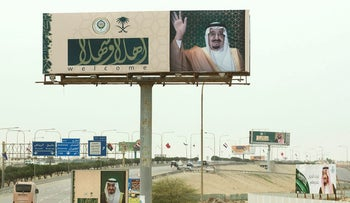 """Billboards with photos of Saudi King Salman and Arabic that reads, """"welcome"""" line the road to the convention center where Arab leaders are meeting for an Arab  summit meeting in Dhahran, Saudi Arabia, Sunday, April 15, 2018"""