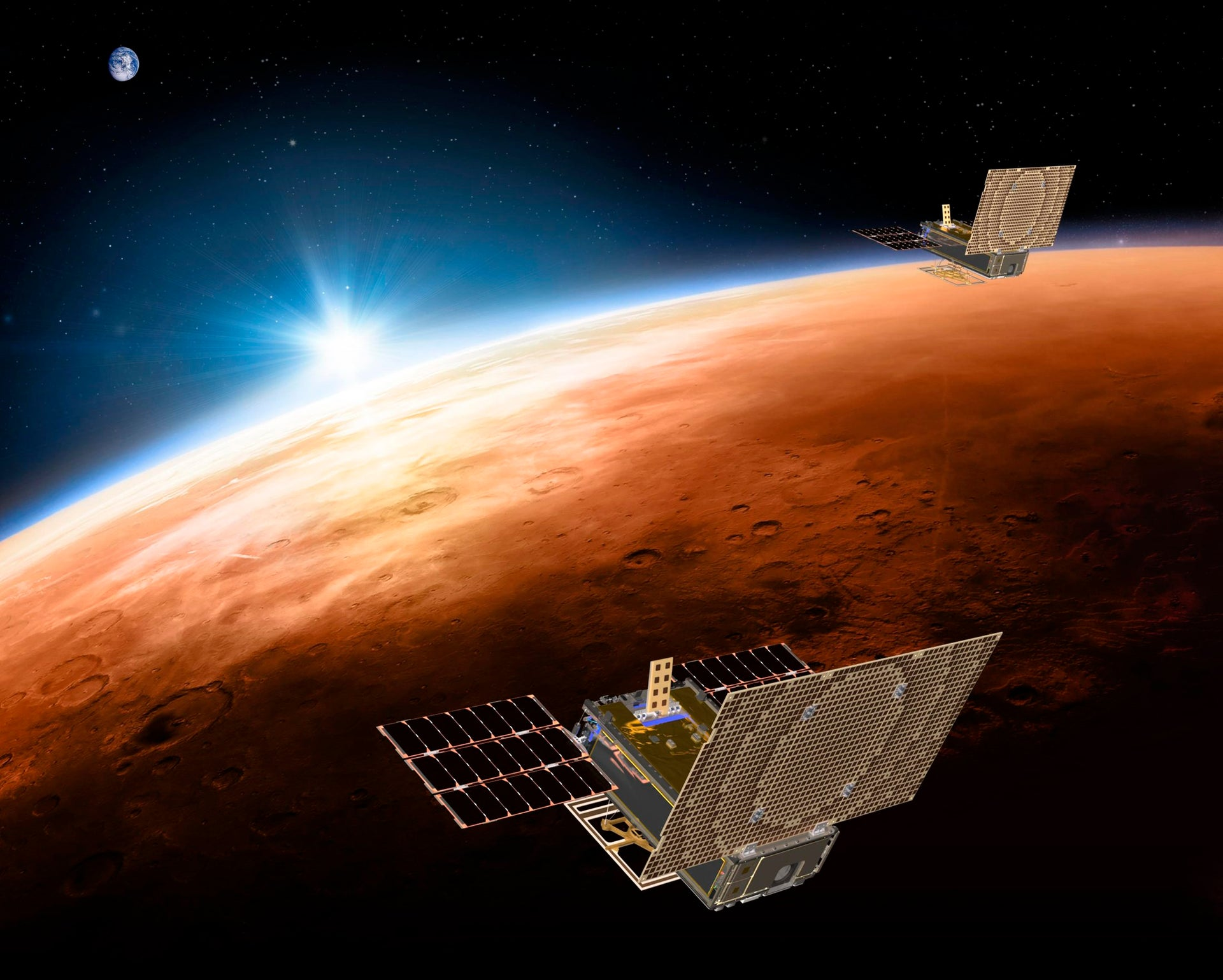 illustration made available by NASA on March 29, 2018 shows the twin Mars Cube One (MarCO) spacecraft flying over Mars with Earth and the sun in the distance.