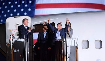 U.S. President Donald Trump applauds as detainee Kim Dong-chul gestures upon his return with Kim Hak-song and Tony Kim after they were freed by North Korea, at Joint Base Andrews in Maryland on May 10, 2018.