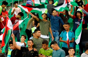 Spectators waving the Palestinian flag during an international friendly soccer match between Iraq and Palestine in Basra, Iraq, on May 8, 2018.