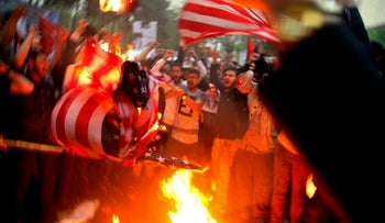 Iranian demonstrators burn representations of the U.S. flag during a protest in front of the former U.S. Embassy in response to President Donald Trump's decision Tuesday to pull out of the nuclear deal and renew sanctions, Tehran, Iran, Wednesday, May 9, 2018.