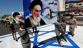 Supporters of Hezbollah brigades march on an Israeli flag with a portrait of late Iranian leader Ayatollah Khomeini and Iran's supreme leader Ayatollah Ali Khamenei, Baghdad, Iraq, June 23, 2017.