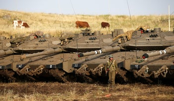 An Israeli soldier stands next to tanks in the Golan Heights, Israel May 10, 2018.