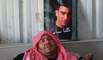 Khaled al-Ja'ar with a picture of his son, Sami, at a mourners tent near his Rahat home in January 2015.
