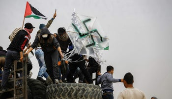 Gaza protesters hold a kite with a swastika painted on it, April 2018.
