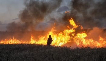 Israeli firefighters try to extinguish a fire near Gaza on May 8, 2018 after it was caused by incendiaries tied to kites flown by Palestinians.