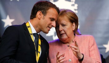 French President Emmanuel Macron talks to German Chancellor Angela Merkel in Aachen, Germany, May 10, 2018