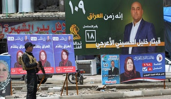 An Iraqi policeman guards a checkpoint by electoral posters in the old town of Mosul on May 11, 2018.