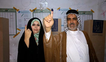 A man and his wife show their ink-stained fingers after casting their votes in the country's parliamentary elections in Baghdad, Iraq, May 12, 2018.