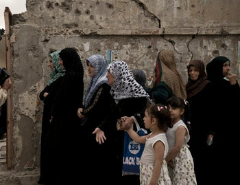 An Iraqi woman gestures to her daughters after waiting in a long line to cast her vote in the country's parliamentary elections at a polling site in a damaged building in west Mosul, May 12, 2018.
